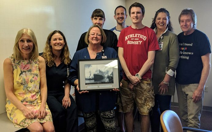 Stephen with hospital staff holding framed photo of the Titanic